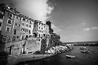 Black and white photo of cliffside buildings in Riomaggiore, Italy.