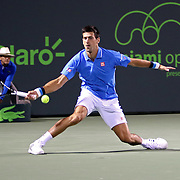Novak Djokovic, of Serbia, slides as he returns a shot from Martin Klizan, of Slovakia,  during their match at the Miami Open tennis tournament on Saturday, March 28, 2015 in Key Biscayne, Florida. Djokovic defeated Klizan 6-0, 5-7, 6-1. (AP Photo/Alex Menendez)