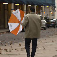 Man with Evening Standard umbrella walking in strong wind, London