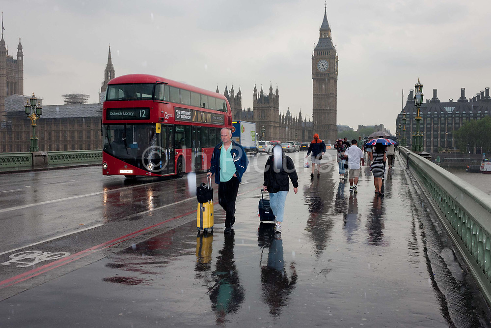 During a downpour, an afternoon of heavy rain in London, drenched and wet tourists and visitors cross Westminster Bridge, England on 7th June 2016. Some carry umbrellas and others endure the rainfall which has been caught as highlighted spots by the cameras flash. A number 12 Routemaster bus passes-by and the path and road glisten with excess water.