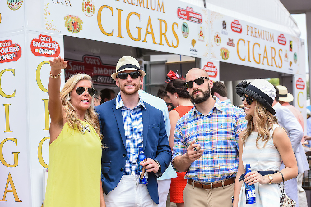 Courtney Dorsey, left, of Ashland, Ky., points to landmarks at Churchill Downs to Kyle Welker, Michael Leonard and Megan Bogdan, all of Pittsburg, Pa., after purchasing cigars at the Cox's Smokers Outlet booth at the 142nd running of the Kentucky Derby. May 7, 2016