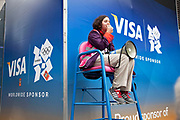 London 2012 Olympic Park in Stratford, East London. Volunteer gives information to people approaching the park through a loud hailer, sitting in front of some advertising for one of the main sponsors, VISA.