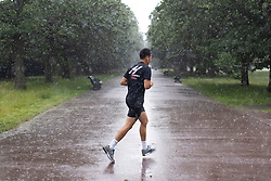 © Licensed to London News Pictures. 27/07/2021. London, UK. A man jogs during heavy rain in Greenwich Park in South East London. A yellow weather warning for thunderstorms is in place for parts of England. Photo credit: George Cracknell Wright/LNP