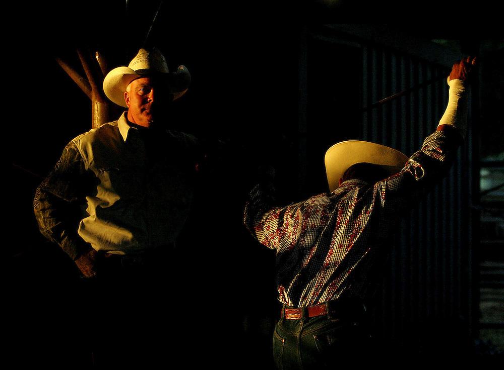 Cowboy Jimmy Joe Bustos chats with bull rider Bobby Mote as Mote stretches before his ride at the Molalla Buckeroo.