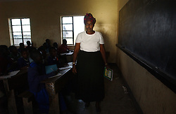 Margaret teaches class 3 at the Endulen Primary school in Ngornogoro District in Tanzania September 29, 2003. She is the only Masai teacher in the school. The Masai were thrown out of the Crater in 1972 and struggle to hang onto the lands they live on now because of increasing pressure from conservationists. (Ami Vitale)