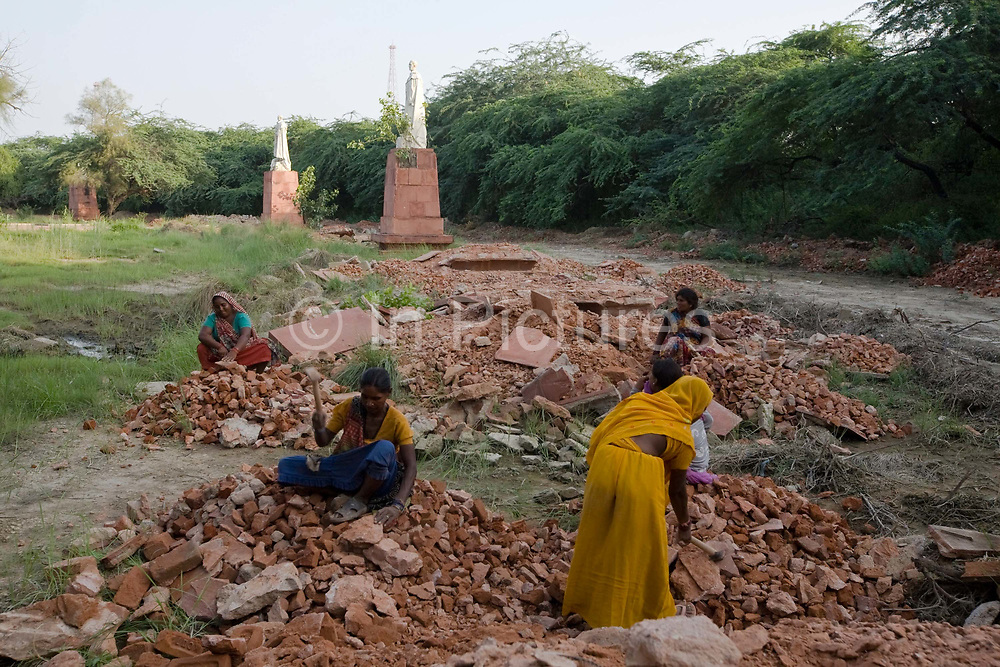 Women demolish plinths and pavement around statues of King George V and other Imperial notables and Viceroys at the Coronation Durbar site near Delhi, India. The statues were removed from New Delhi in the 1960's. The statue of George V originally stood under the canopy of India in Rajpath.