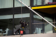 A window cleaning contractor wipes glass while abseiling down the side of high-rise apartments at Nine Elms, Battersea, during the second lockdown of the UK's Coronavirus pandemic, when all but essential retailers and businesses remain shut according to the government's restriction rules, on 13th November 2020, in London, England.