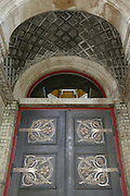 """Details of restored metalwork by Benham & Froud on a door of the old Abbey Mills Pumping Station (Station A). The cupola can be seen through the window which assisted in providing ventilation for the original steam beam engines. The stone carving shows examples of local flora. Located in Abbey Lane, London E15, the building is a sewerage pumping station, designed by engineer Joseph Bazalgette, Edmund Cooper, and architect Charles Driver, it was built between 1865 and 1868 after an outbreak of cholera in 1853 and """"The Big Stink"""" of 1858. It was designed in a cruciform plan, with an elaborate Byzantine style, described as The Cathedral of Sewage. The pumps raise the sewage in the London sewerage system between the two Low Level Sewers and the Northern Outfall Sewer, which was built in the 1860s to carry the increasing amount of sewage produced in London away from the centre of the city."""