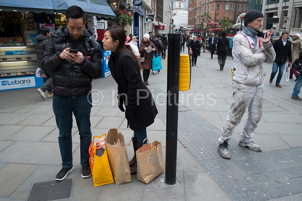 Well dressed Chinese couple and a workman with paint covered overalls in the City of London, England, United Kingdom.
