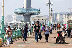 Licensed to London News Pictures. 06/09/2021. Brighton, UK. Walkers enjoy the hot sun on Brighton Beach, East Sussex as weather forecaster predict a mini-heatwave for September this week with temperatures hitting over 29c tomorrow. Photo credit: Alex Lentati/LNP