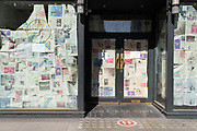 Sheets of old newspapers cover the window of the closed branch of All Bar One on New Oxford Street, during the third lockdown of the Coronavirus pandemic, on 29th March 2021, in  London, England.
