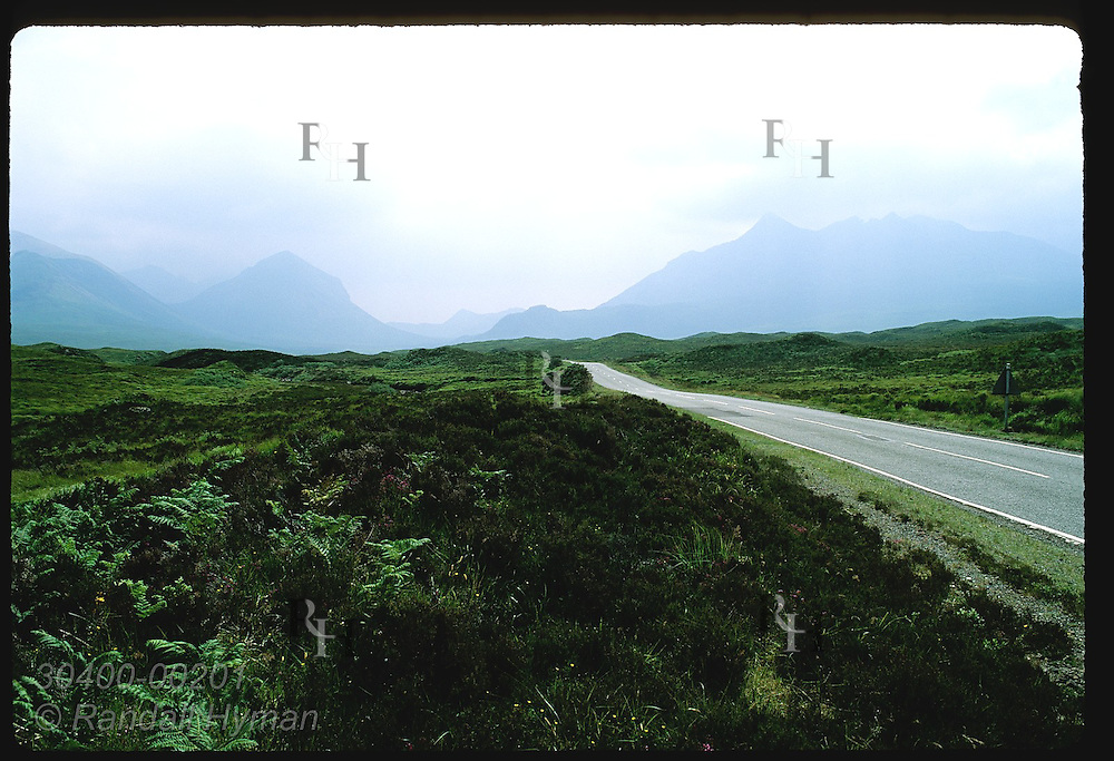 Highway beelines toward rugged mountains on a stormy July morn on the Isle of Skye. Scotland