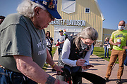 10 OCTOBER 2020 - DES MOINES, IOWA: US Senator JONI ERNST autographs a picture for a Korean War veteran at a campaign event. Sen. Ernst is on a ride across Iowa. She left Sioux City Saturday morning and stopped in Carroll, IA, before ending the day's ride in Des Moines at Big Barn Harley-Davidson. She had a rally in the parking lot of the Harley-Davidson dealership. The ride is a fundraiser for the Puppy Jake Foundation (which provides service animals to veterans) and the Greater Cedar Rapids Community Foundation's Derecho Disaster Recovery. About 50 people rode with Sen Ernst from Carroll to Des Moines and another 80 were waiting for her in Des Moines.     PHOTO BY JACK KURTZ