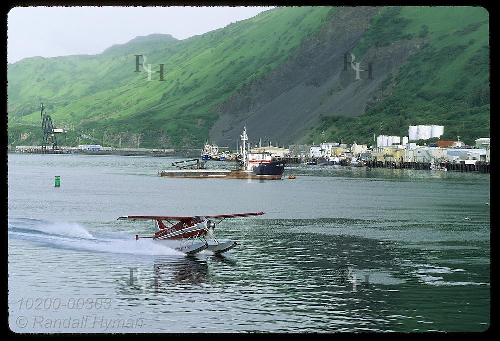 Seaplane lands in harbor at town of Kodiak on an overcast July morning; Kodiak Island, Alaska