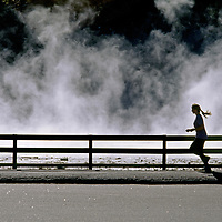 Yellowstone National Park, Wyoming. A woman jogs past steaming springs.