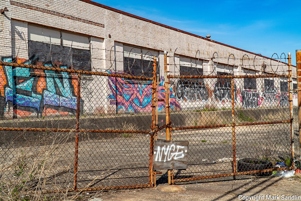 Graffiti, barbed wire and locked gates on warehouse that backs up to the Beltline