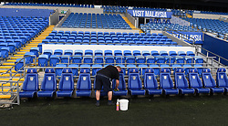 Groundsmen prepare the dugout before the Premier League match at the Cardiff City Stadium.