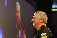 Devon Petersen celebrates on the big screen as Wayne Jones looks on during the World Championship Darts 2018 at Alexandra Palace, London, United Kingdom on 17 December 2018.