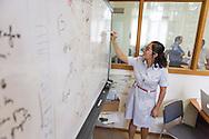 A young woman writes on a whiteboard, Hanoi, Vietnam, Southeast Asia