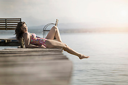 Mature woman lying in swimsuit on pier, Bavaria, Germany
