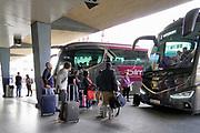 Spanje, Vlencia, 4-11-2019 Op het centrale busstation van deze grote stad komen en gaan bussen naar veel andere steden in het land. Het reizen met de bus is in spanje een goedkoop alternatief . Er zijn verschillende busmaatschappijen . Mensen wachten of nemen afscheid . Chauffeurs roken nog even een een sigaret . Reizen met de bus, autobus . Foto: Flip Franssen
