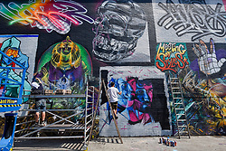 "© Licensed to London News Pictures. 28/05/2018. LONDON, UK. Street artists (L to R) Jim Vision and Core246 at work at ""Meeting of Styles"" near Brick Lane in East London.  The three day festival celebrates street art, with artists from around the world demonstrating their skills.  Photo credit: Stephen Chung/LNP"