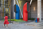 Woman wearing a red dress interacts with the red and blue air ducts shaped like funnels, which are part of Vents 88 on London Wall by architect Richard Rogers, appear as strange architectural elements in the City of London, England, United Kingdom. 88 Wood Street is a commercial office tower development in the City of London, England. The architects were Richard Rogers Partnership, now known as Rogers Stirk Harbour + Partners. The building was constructed between 1993 and 2001 and was known as one of the Rogers buildings which placed normally concealed internal elements like ventilation ducts on the outside of the building allowing more internal space.