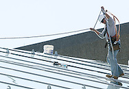 New Paltz, New York - A man works on glass panels on the roof of the addition to the Student Union Building at the SUNY New Paltz.  The addition is clad in 315 panels of energy-efficient glass. March 22, 2010.