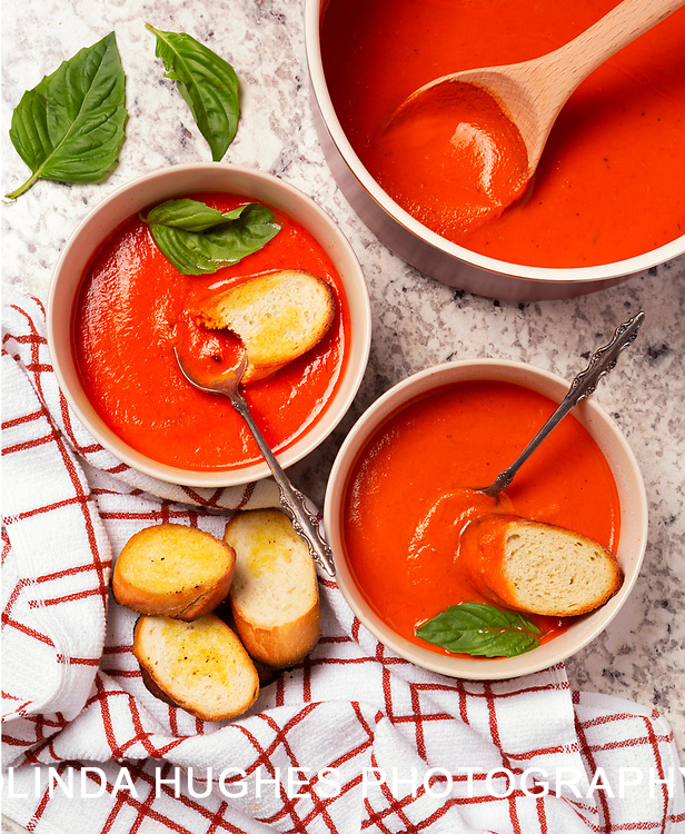 Overhead view of homemade tomato basil soup with bread on a granite surface