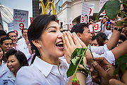 "17 FEBRUARY 2013 - BANGKOK, THAILAND:  Thai Prime Minister YINGLUCK SHINAWATRA performs a ""wai"" (traditional Thai greeting) while campaigning for Pongsapat Pongchareon in Bangkok Sunday. Pol General Pongsapat Pongcharoen, a former deputy national police chief who also served as secretary-general of the Narcotics Control Board is the Pheu Thai Party candidate in the upcoming Bangkok governor's election. (He resigned from the police force to run for Governor.) Former Prime Minister Thaksin Shinawatra reportedly recruited Pongsapat. Most of Thailand's reputable polls have reported that Pongsapat is leading in the race and likely to defeat Sukhumbhand Paribatra, the Thai Democrats' candidate and incumbent. The loss of Bangkok would be a serious blow to the Democrats, whose base is the Bangkok area.     PHOTO BY JACK KURTZ"