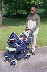 Young father walking through park pushing baby in pram,