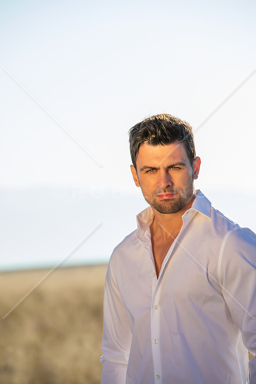 good looking man with green eyes in a white button down shirt outdoors