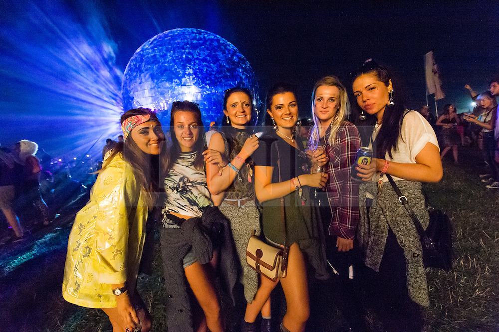 © Licensed to London News Pictures. 04/09/2014. Isle of Wight, UK. Festival goers enjoy the nighttime music and DJ's alongside a giant glitter ball  at Bestival 2014 Day 1.  Bestival organisers claim the glitter ball to be the largest in the world and Guinness World Records officials will arrive to judge this.  Disco legend Chic (featuring Nile Rodgers) will be performing as Sunday night headliner to close the festival.   The weather has been warm and sunny. Photo credit : Richard Isaac/LNP