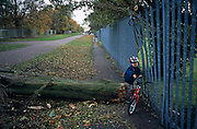 A young boy edges through a gap between some railings and the end of a fallen tree trunk that has fallen across a footpath. The child is on his way to nursery school and the night before strong winds brought down trees in the south London area and cause disruption to transport infrastructure. It is an adventure for this child who isn't bothered in the slightest at this minor inconvenience to his journey, a route he takes with his mother or father every morning. Pushing his bike first, he takes care not to hurt himself on the jagged timber