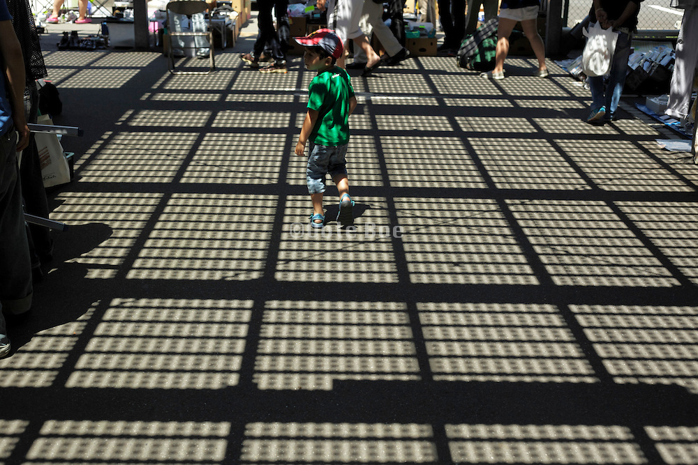 child standing with sunlight pattern from grid above