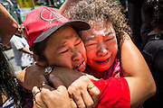"""25 MAY 2014 - BANGKOK, THAILAND: Thai """"Red Shirt"""" supporters of the ousted civilian government cry at a demonstration against the military junta. A family member of the woman on the left had been arrested by soldiers. Public opposition to the military coup in Thailand grew Sunday with thousands of protestors gathering at locations throughout Bangkok to call for a return of civilian rule and end to the military junta.     PHOTO BY JACK KURTZ"""