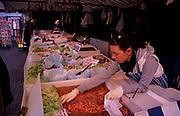 A3A9J2 Fish stall Ipswich market Suffolk England with female assistant picking up fish for a customer. Image shot 2006. Exact date unknown.
