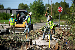 26 August 2015. New Orleans, Louisiana. <br /> Hurricane Katrina revisited. <br /> Rebuilding the Lower 9th Ward a decade later. <br /> Contractors working with the City repair roads and sidewalks in areas still devastated by the storm. The hope is that in fixing the roads, people will be encouraged to return. Signs of a rebirth of the community following the devastation of hurricane Katrina a decade earlier.<br /> Photo credit©; Charlie Varley/varleypix.com.
