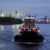 Capt. Matt Register pilots the J.P. McAllister, of McAllister Towing in Wilmington, N.C., back toward the docks on the Cape Fear River. The Tugboats Margaret McAllister and Kathryne E. McAllister helped guide and dock the Yang Ming Elixir, an 882-foot long container ship with approximately 2,000 cargo containers at the North Carolina State Port at Wilmington.  Photo by Mike Spencer<br /> <br /> McAllister Towing of Wilmington, N.C. is one of 17 locations along the U.S. East Coast owned and operated by McAllister Towing & Transportation. Locally the company has three tugboats in service. The workhorse of the trio, the Tractor Tug Margaret McAllister works alongside tugboats J.P. McAllister and Kathyrne E. McAllister to dock container ships like the Yang Ming Elixir, an 882-foot long container ship with approximately 2,000 cargo containers at the North Carolina State Port at Wilmington. Captain Glenn E. Turbeville, Vice President of McAllister Towing of Wilmington, N.C. oversees the local fleet of tugs and crew. Each tugboat typically has a crew of three that includes a Captain, Engineer and a deckhand.