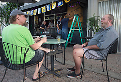 Two patrons have a drink at a sidewalk bar as it is been boarded up in preparation for hurricane Irma Friday, September 8, 2017 in Hollywood, FL, USA. Photo by /Paul Chiasson/CP/ABACAPRESS.COM
