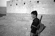A teenage Peshmerga near a government prison where civilians were tortured and executed during Saddam Hussein's genocide against the Kurds.