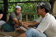 Ecuador, May 8 2010: A Huaorani staff member rubs wood shavings on Jorge's forearm. In Huaorani tradition this transfers knowledge and skills to the recipient. Copyright 2010 Peter Horrell