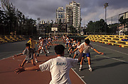 An exercise class for schoolchildren on a basketball court at a sports ground in the highly-populated Asian city, on 10th August 1994, in Macau, China. Macau is now administered by China as a Special Economic Region SER, home to a population of mainland 95% Chinese, primarily Cantonese, Fujianese as well as some Hakka, Shanghainese and overseas Chinese immigrants from Southeast Asia and elsewhere. The remainder are of Portuguese or mixed Chinese-Portuguese ancestry, the so-called Macanese, as well as several thousand Filipino and Thai nationals. The official languages are Portuguese and Chinese.