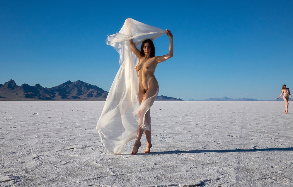 Photo of a nude woman posing on the Bonneville Salt Flats, Utah waving a long scarf and anothr model out of focus in the background
