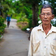 CAPTION: Mai Van Cho, standing in between his house and the river, next to an erosion barrier that he's in the process of constructing. LOCATION: An Binh Ward, Can Tho, Vietnam. INDIVIDUAL(S) PHOTOGRAPHED: Mai Can Cho.