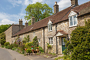Row of attractive old stone cottages in village of Mells, Somerset, England, UK