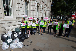 © Licensed to London News Pictures. 08/08/2019. London, UK. Peoples Vote activists dressed as waste collectors dump filled bin bags and plastic rats outside the Cabinet Office. They are protesting against a No Deal Brexit .  Photo credit: George Cracknell Wright/LNP