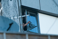 © Licensed to London News Pictures. 14/06/2017. London, UK. A distressed, trapped man waves an item of clothing from his window, at the scene of a huge fire at Grenfell tower block in White City, London. The blaze engulfed the 27-storey building with 200 firefighters attending the scene. There were reports of people trapped in the building. Photo credit: Guilhem Baker/LNP