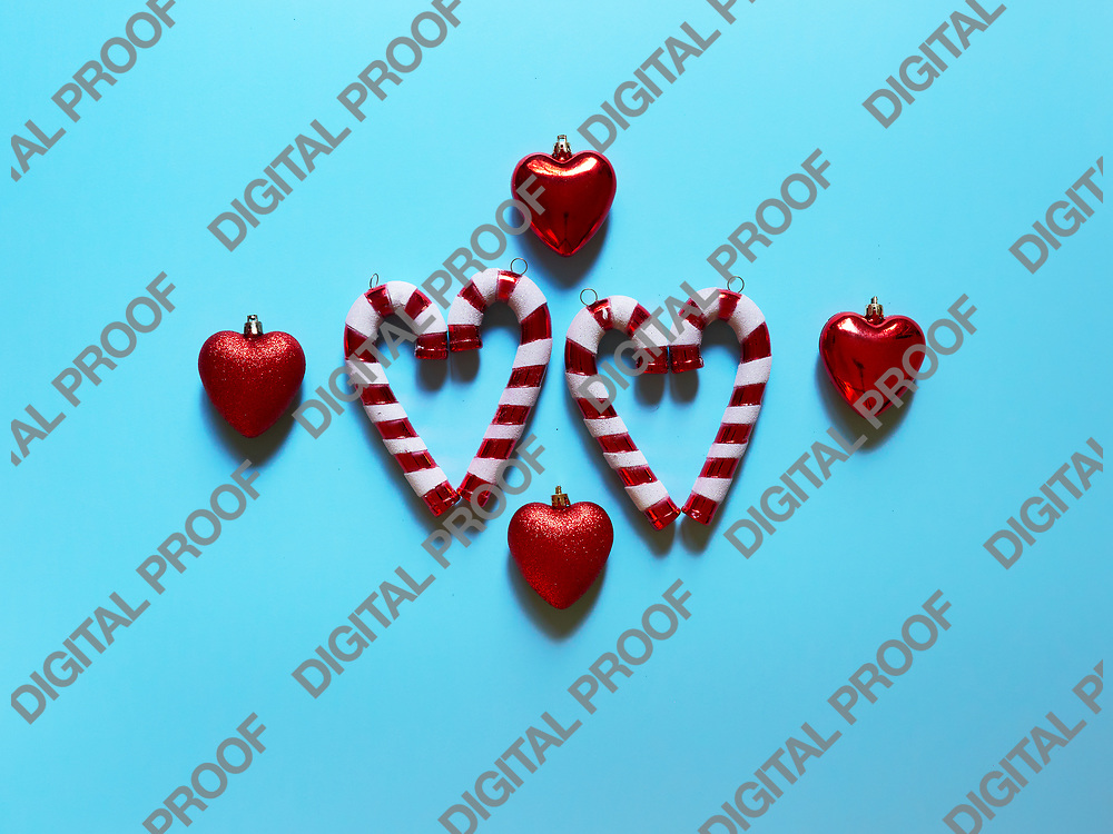 Christmas candy cane and hearts at studio above view over a light blue background isolated flatlay