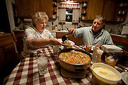 Gordon Stine, a farmer, ladles out hearty homemade vegetable and beef stew for his wife, Denise, after a day of corn harvesting at their farm in St. Elmo, Illinois.    (From the book What I Eat: Around the World in 80 Diets.) The caloric value of his day's worth of food in the month of September was 4,100 kcals. He is 56 years old; 5 feet, 9 inches tall; and 245 pounds. MODEL RELEASED.